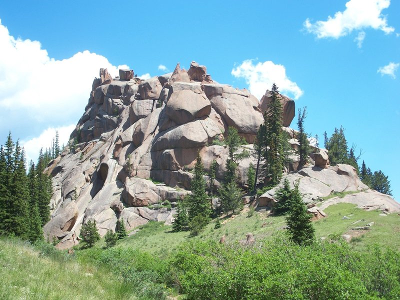 A towering rock formation stands guard near the stream crossing on The Crags Trail.