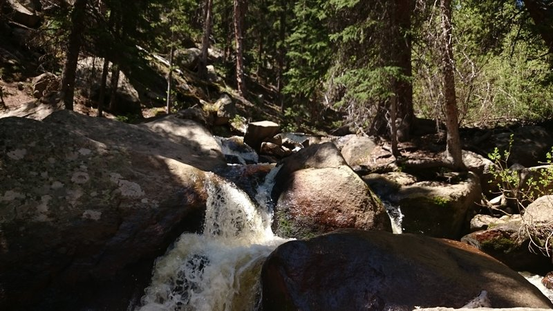 Multiple small, cascading waterfalls flow along Rough And Tumbling Creek.
