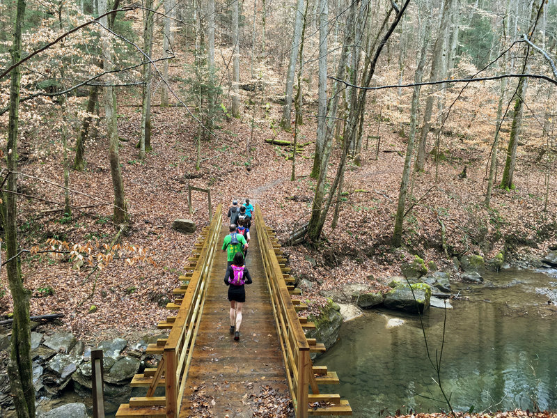 Runners navigate a bridge crossing at the intersection of Lick Creek Trail and the Sheltowee Trace.