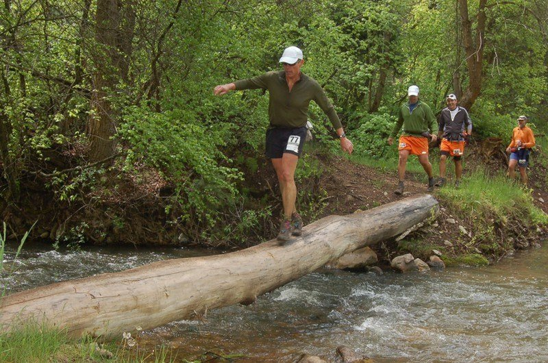Runners navigate a log crossing of the Left Fork Hobble Creek at about mile 28 of the Squaw Peak 50 Mile Trail Run.