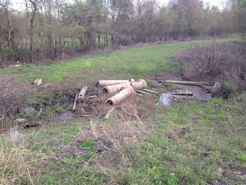 A pile of debris offers access across the wet ditch to the north end of the Addicks-Fairbanks Trail.