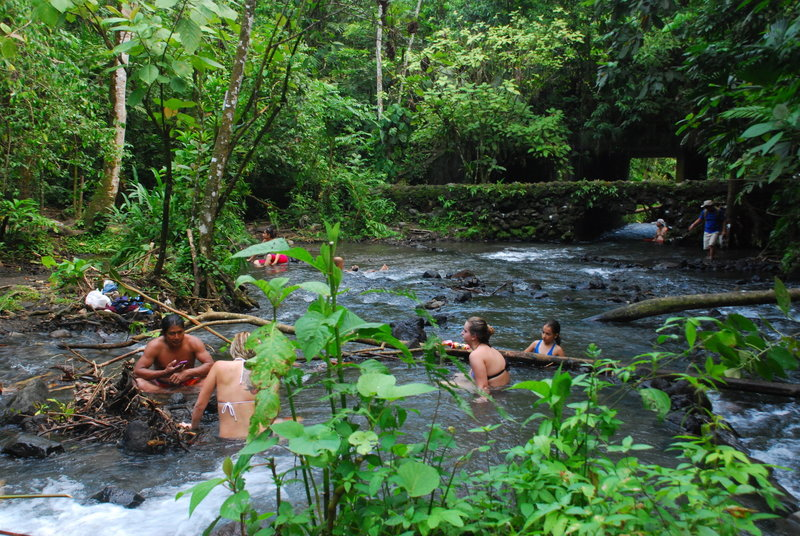 Friends soak in the natural hot springs near Tabacon.
