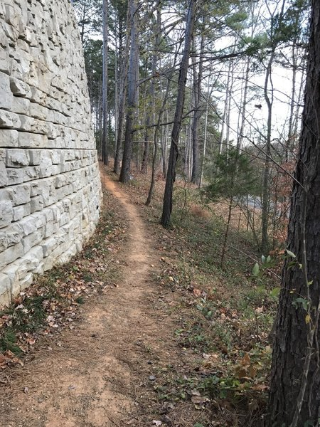 The Chesley Creek Loop travels beside the retaining wall for the Blue Ridge School athletic fields.
