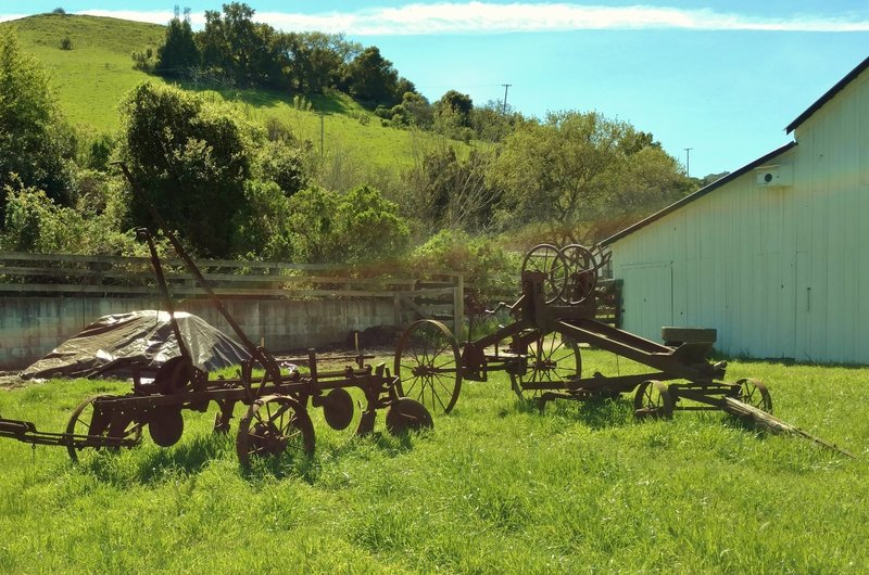 Old ranch machinery stands outside the historic ranch house and grounds.