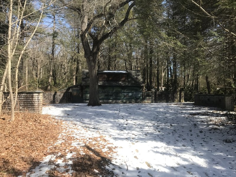 A carriage house stands shaded in the woodlands of Maudslay State Park.