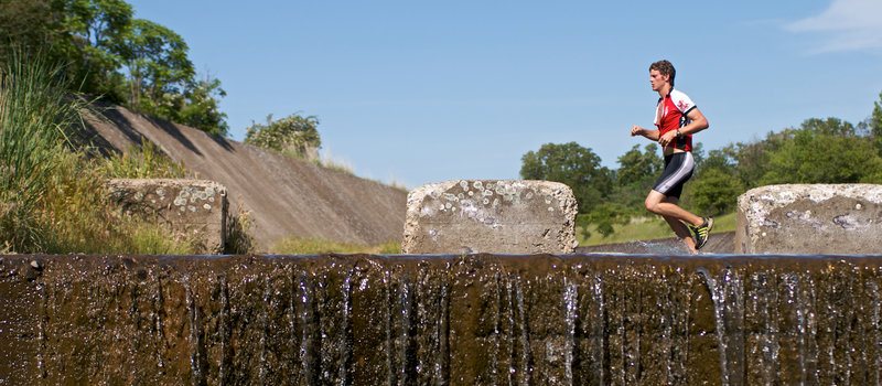 An athlete charges through the spillway canal that characterizes the Meadowlark Trail.