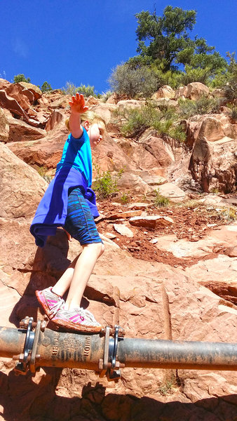 A child tries her hand at traversing a pipe along the Kanarra Creek Trail.