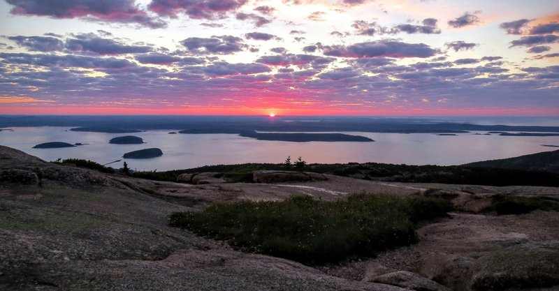 The sun rises over Cadillac Mountain and the archipelago.