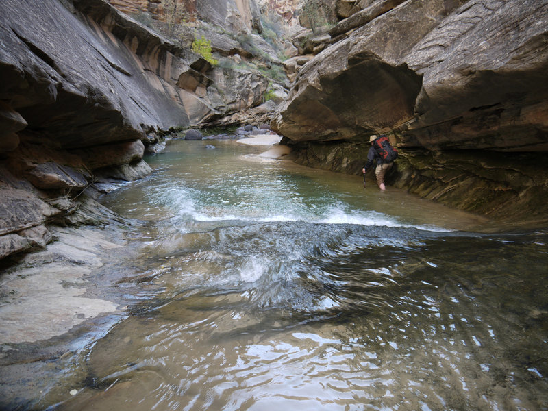 A hiker edges through the narrows of Lower Death Hollow.