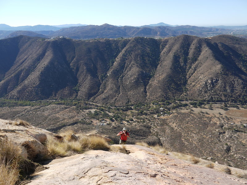 A hiker ascends the steep prow of El Cajon Mountain.