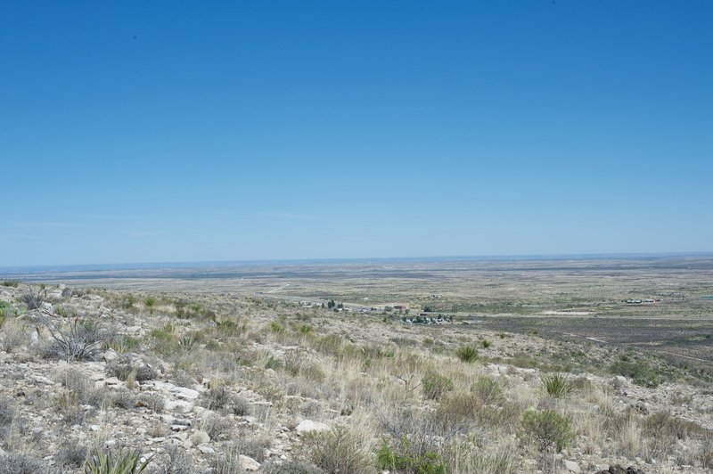 The first glimpse of Whites City comes into view while the New Mexico landscape stretches out beyond.