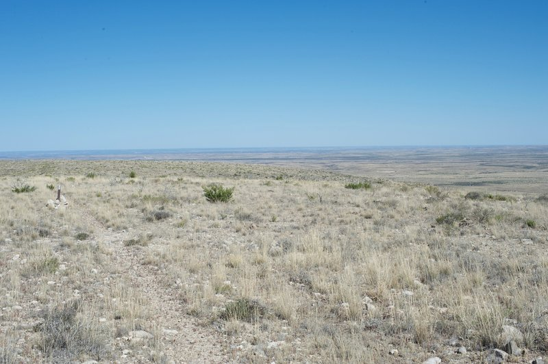 The trail can be seen following the cairns and markers off into the distance, while the New Mexico landscape stretches off on the right side of the trail.