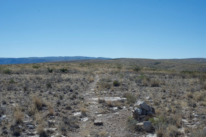 Cairns and posts mark the path as it makes its way toward the visitor center, which sits off in the distance.