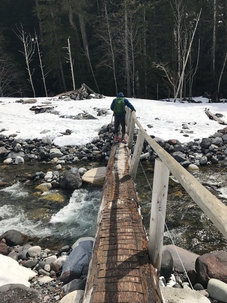 A hiker crosses the log bridge at the wonderland trailhead via Carter Falls/Longmire entrance.