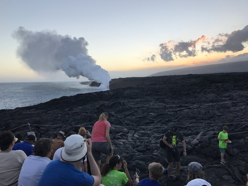 A mass of people watch the sunset at the Kamokuna ocean lava viewing area.