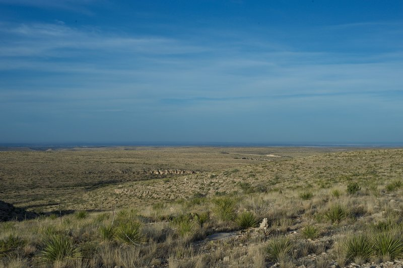 When the trail crests the ridge, views of the desert spread out before you. You can see the park boundary fence and cairns that mark the trail.