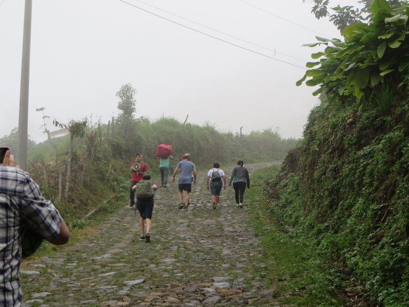 The group walks up the hill to Aldea la Trinidad Tajumulco