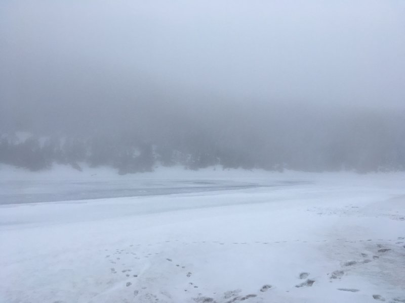 Frozen Kinsman Pond can be seen through the fog.
