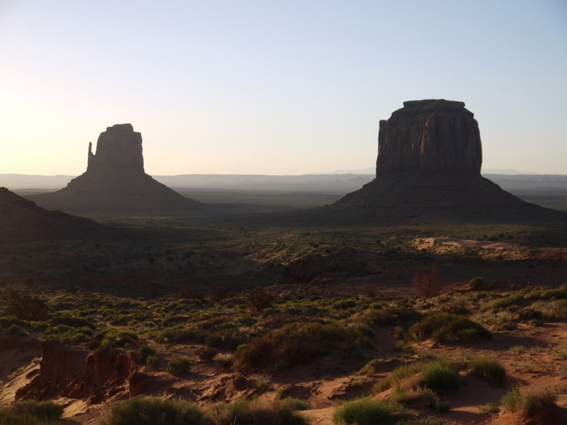 Two buttes at Monument Valley cast shadows over the land in the early morning light.