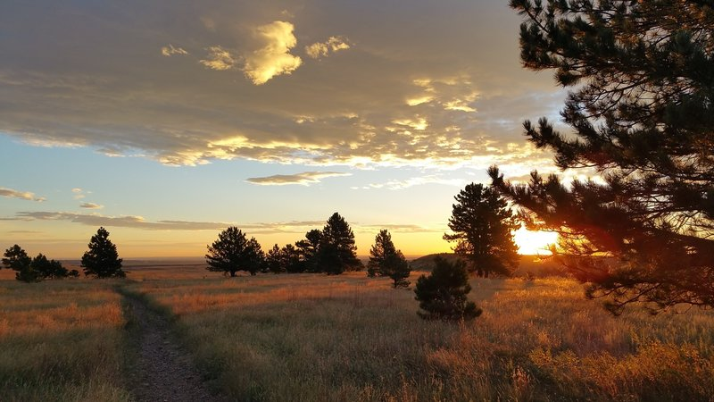 A lovely sunrise, heading east on the trail. Wear a hat with a brim! September 2015.