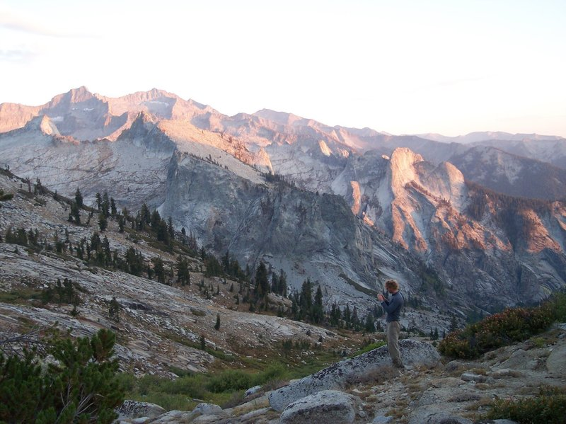A hiker photographs the sunset on the ridge.