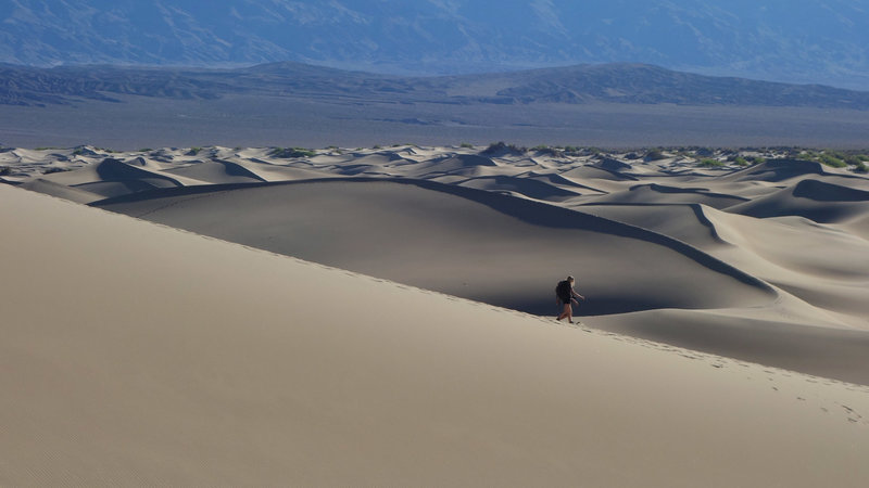 An early morning hiker sinks her soles into the Mesquite Sand Dunes.