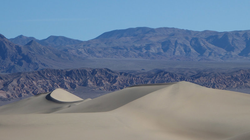 Crescent dunes are framed by the mountains to the west.