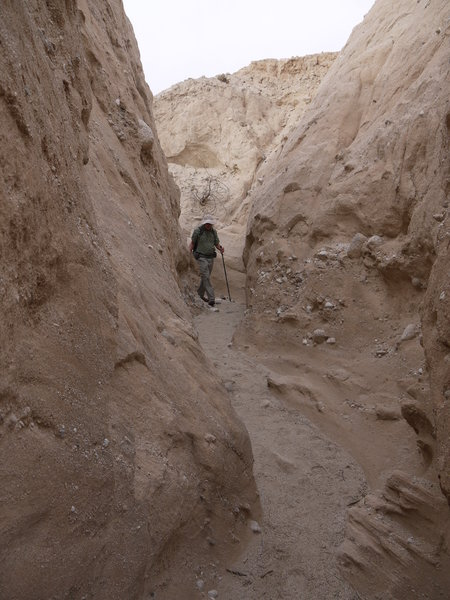 A hiker enters Canyon Sin Nombre 760 Slot Canyon from the top.