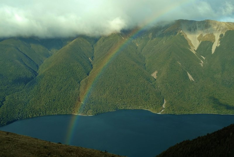 A rainbow forms over Lake Rotoiti on a snow-showery day high on Paddy's Track.