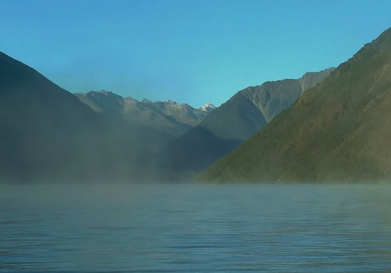 Early morning mist floats atop Lake Rotoiti with the northernmost Southern Alps in the distance.