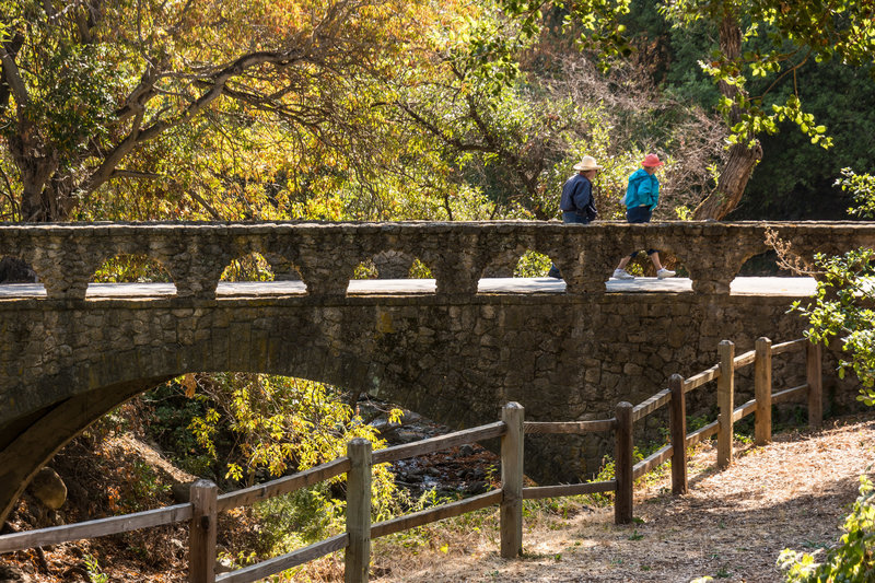 A couple crosses the stone bridge to reach the Penitencia Creek Trail.