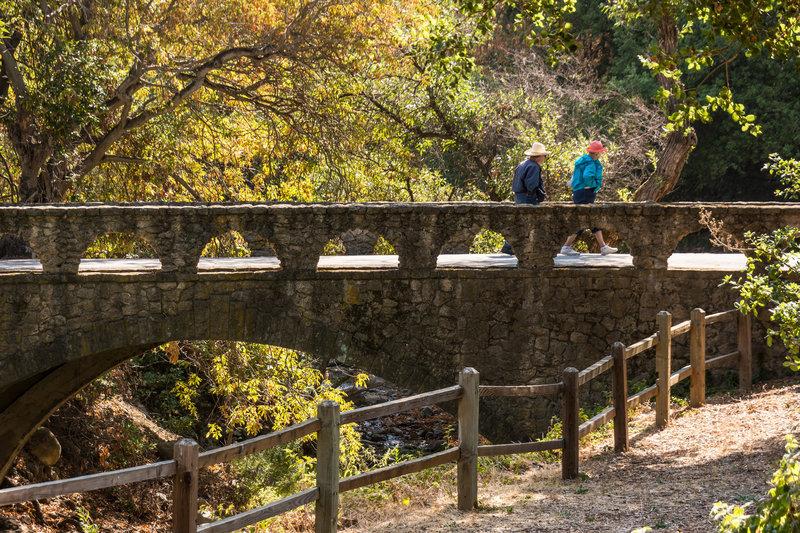 A couple crosses the stone bridge to reach the Penitencia Creek Trail.