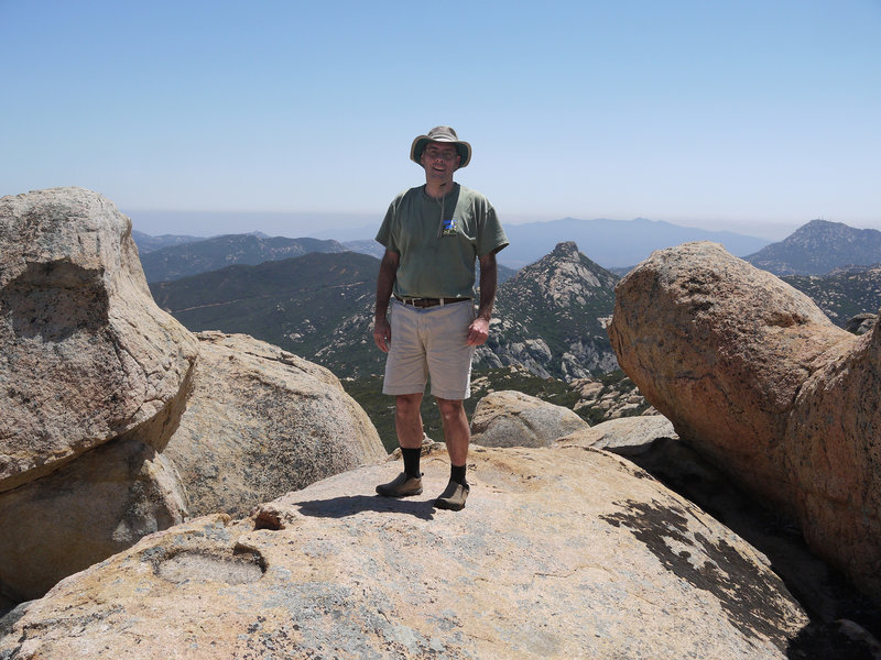 A hiker poses atop Gaskill Peak with Lawson Peak in the center-right.