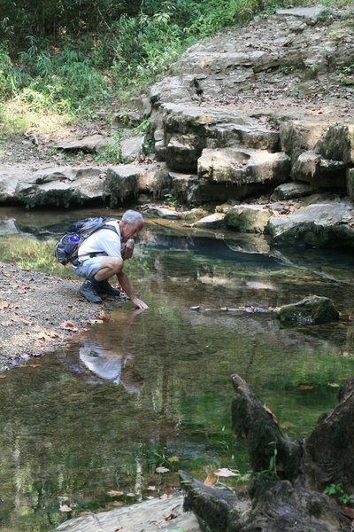 A visitor feels the cool water flowing out of Echo River Springs. Photo credit: NPS Photo.