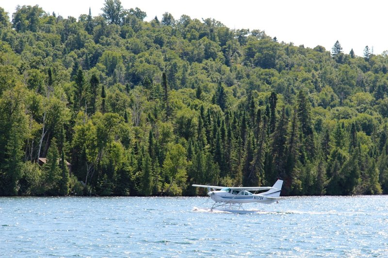 A seaplane daintily lands on the water near Windigo.