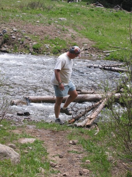 An adventurer builds and tests a log bridge to cross Little Cimarron River during spring flooding.