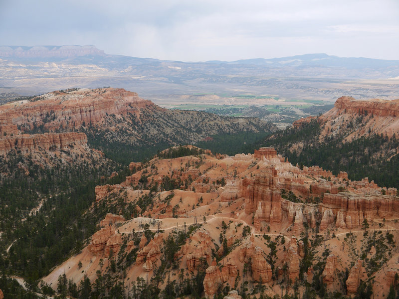 Peekaboo Loop trail in the foreground and the city of Tropic in the distance seen from the Rim Trail in Bryce Canyon National Park.
