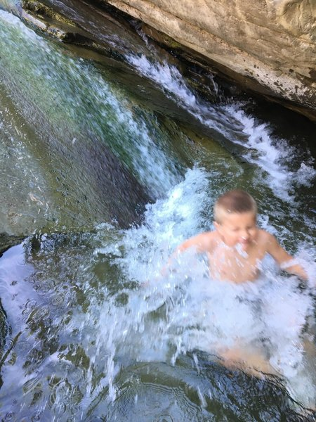 A child slides into a pool in the river next to Cross Camp.