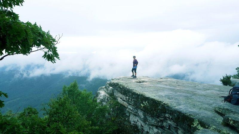 A hiker enjoys her reward on McAfee Knob.