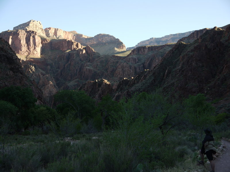 A hiker watches the late-afternoon sun on the canyon wall from near Bright Angel Campground.