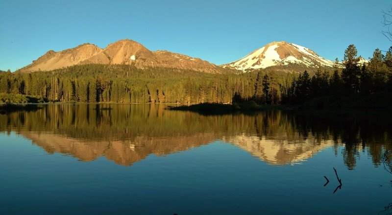 Manzanita Lake mirrors Chaos Crags on the left, and Mt. Lassen on the right, on a warm summer evening.