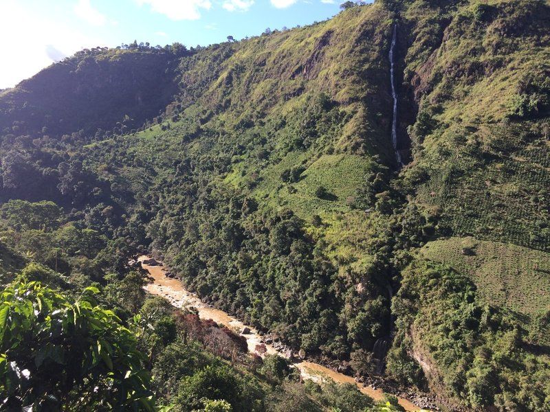 A tall waterfall cascades into the Magdalena River.