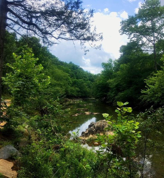 The rocky Eno River flows beside the trail.