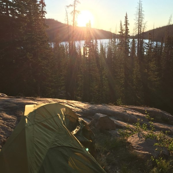 The sun rises over camp on the Rainbow Lake Trail.
