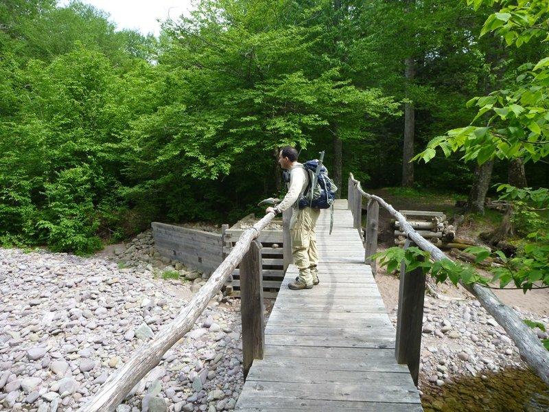 A hiker crosses the East Branch Neversink River.