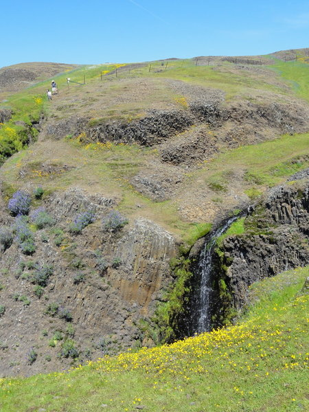 Percolated water creates a small waterfall in front of an old ranching fence at the top of the ridge.