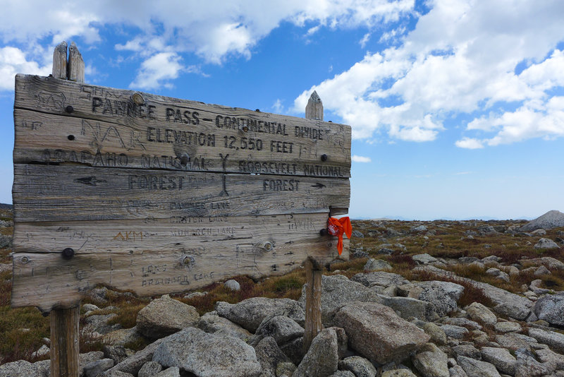 A weathered sign greets you at the pass