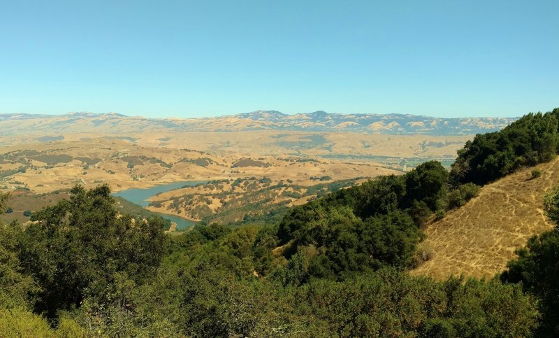 Calero Reservoir with the Santa Teresa Hills behind it, and the Diablo Range in the distance, looking northeast from high on Bald Peaks Trail