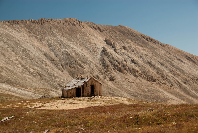 An old mining cabin with an impressive backdrop.