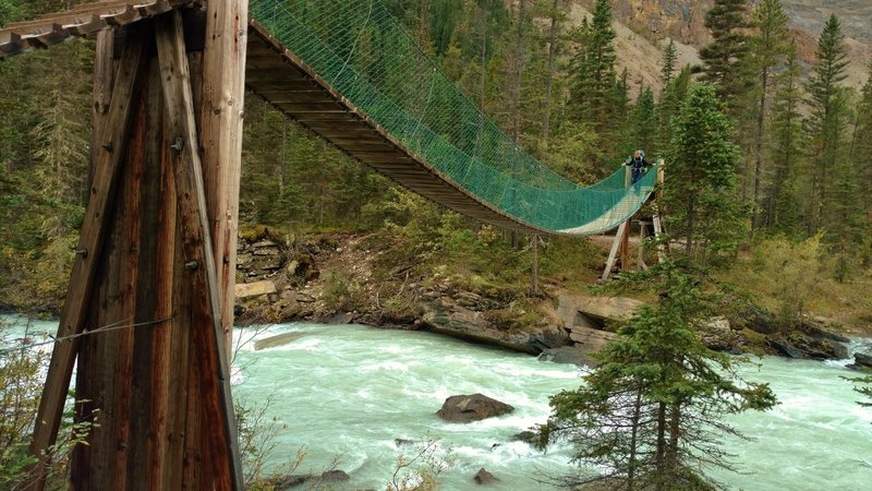 Crossing the swift flowing Robson River on a suspension bridge near the Whitehorn trail camp